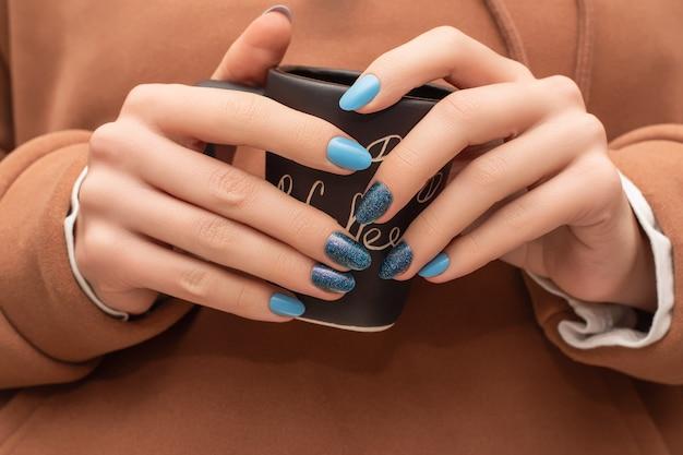 Mani femminili con unghie blu design tenendo la tazza di caffè nero.
