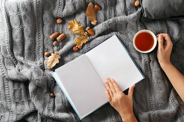 Mani femminili con libro e tazza di tè sul letto