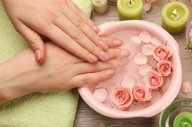 Mani femminili con ciotola di acqua termale aroma sulla tavola di legno, primo piano