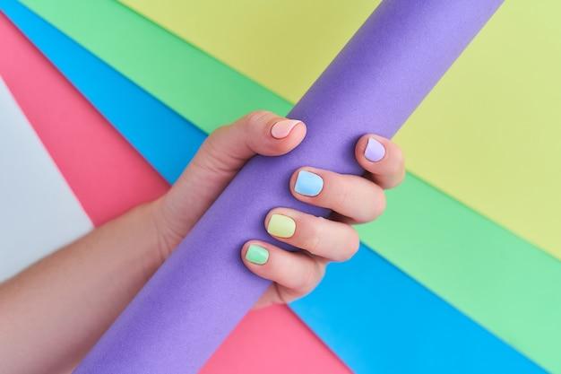 Mani femminili con colori vivaci su uno sfondo colorato