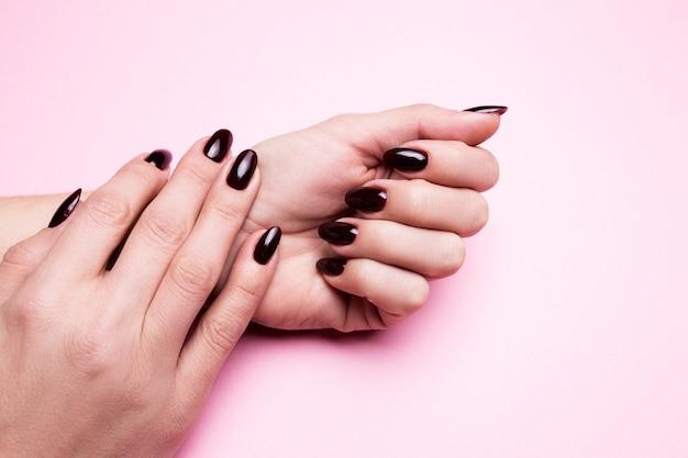 Mani femminili con il manicure bordeaux su uno sfondo rosa isolato.