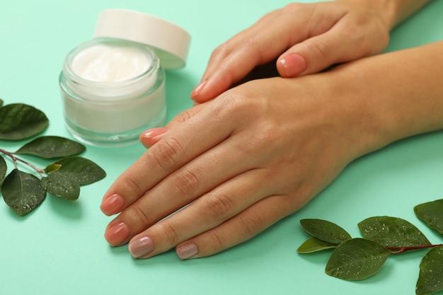 Mani femminili con crema cosmetica