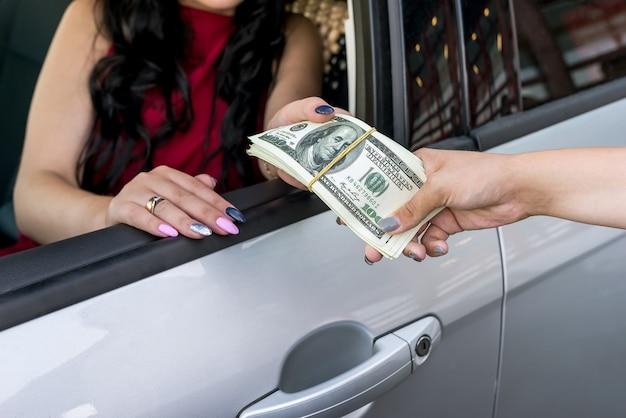 Mani femminili con mazzo di dollari e auto
