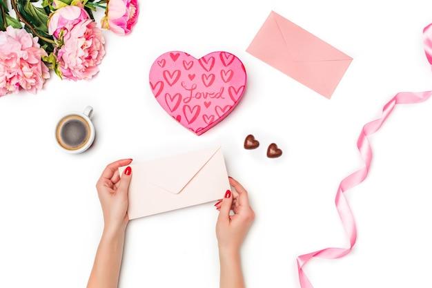 Le mani femminili con busta, confezione regalo, nastro, cuori e foglio bianco di carta e penna su sfondo bianco