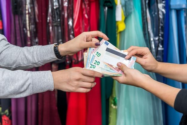 Mani femminili con banconote in euro e carta di credito