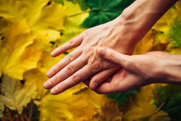 Mani femminili con pelle scolorita close-up su sfondo sfocato del fogliame di autunno