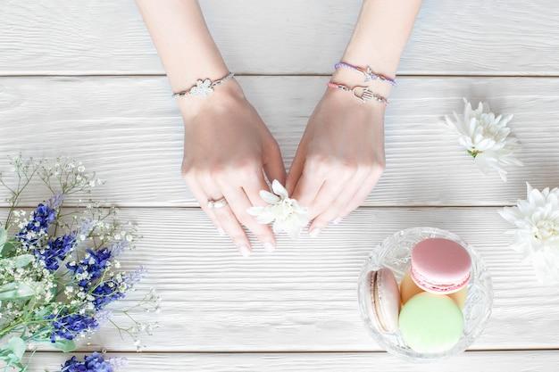 Mani femminili con fiore, piatto laici. vista dall'alto sulle braccia della giovane donna che tiene bel fiore sulla tavola di legno bianca con bouquet e vaso con amaretti colorati