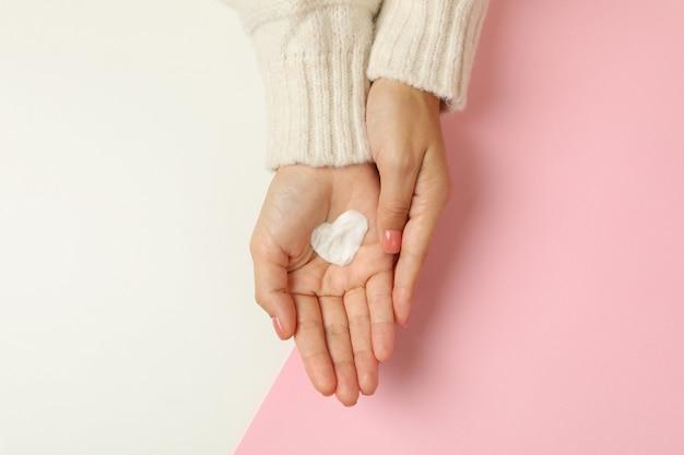 Mani femminili con crema a forma di cuore