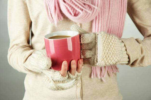 Mani femminili con bevanda di successo, su sfondo chiaro