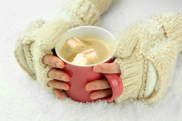 Mani femminili con bevanda di successo, su superficie chiara