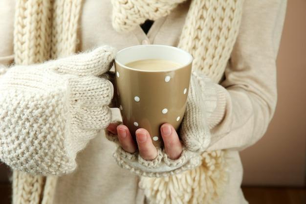 Mani femminili con il primo piano della bevanda calda