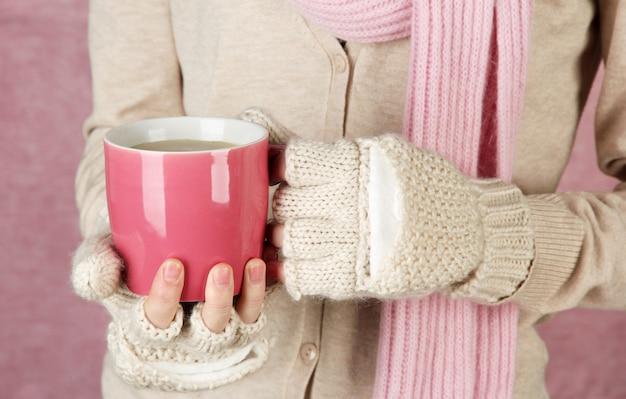Mani femminili con bevanda calda, primo piano