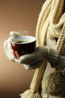 Mani femminili con bevanda calda su sfondo colorato