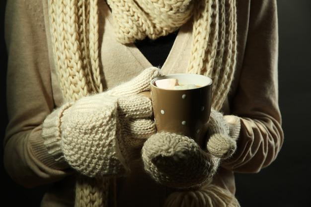 Mani femminili con bevanda calda, su sfondo colorato