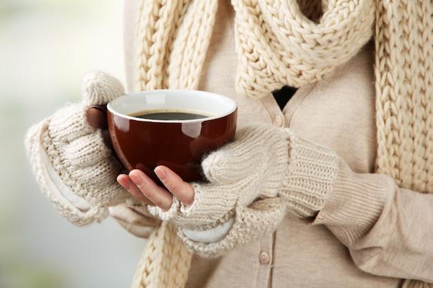 Mani femminili con bevanda calda, su sfondo chiaro