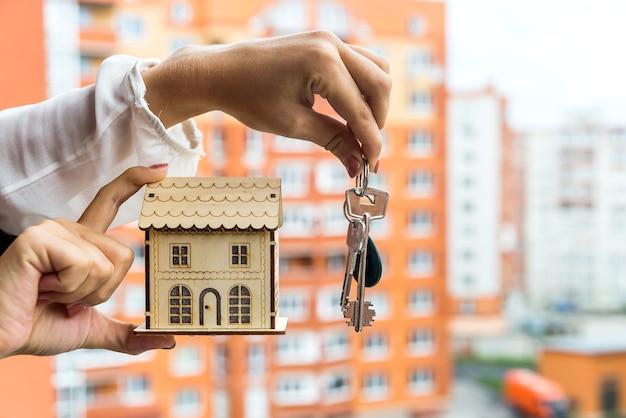 Mani femminili con modello di casa e chiavi, primo piano