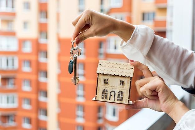 Mani femminili con il modello e le chiavi della casa, primo piano