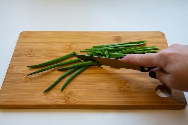 Mani femminili con un coltello, affettare le verdure su una tavola di legno su sfondo bianco. la donna taglia le cipolle verdi