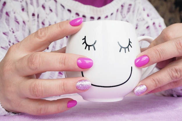 Mani femminili con manicure lilla che tiene una tazza