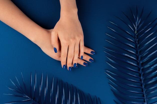 Mani femminili con il manicure di colore blu classico su sfondo blu. avvicinamento