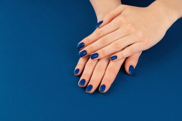 Mani femminili con manicure di classico colore blu. avvicinamento