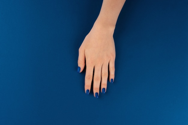 Mani femminili con manicure di classico colore blu