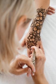 Mani femminili con motivo mehendi di fiori artista che dipinge con l'henné