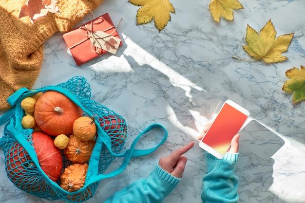 Mani femminili con cellulare, zucche in borsa a tracolla, scarpe bianche, maglione alla menta blu e foglie gialle