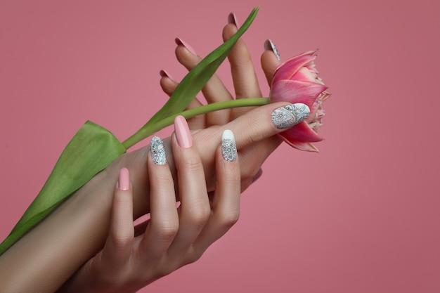 Mani femminili con unghie art design e fiore di primavera