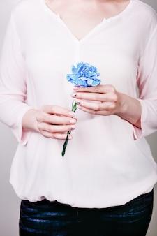Mani femminili con manicure naturale che tiene il garofano