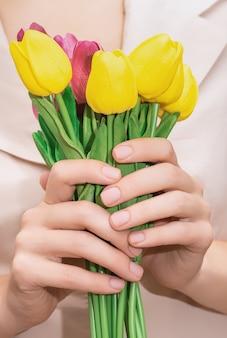 Mani femminili con unghie naturali. manicure per unghie nude. mani femminili che tengono il mazzo di tulipani gialli e rosa.
