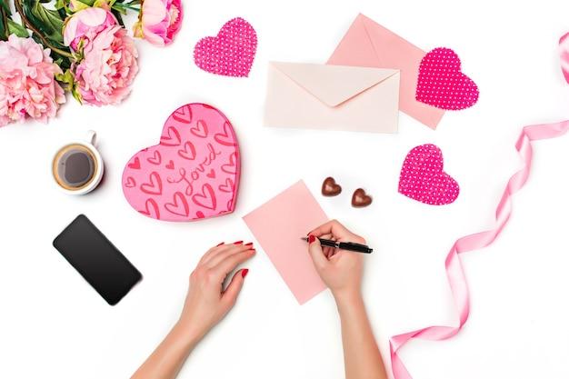 Le mani femminili con penna, confezione regalo, nastro, cuori e foglio di carta bianco e penna su sfondo bianco