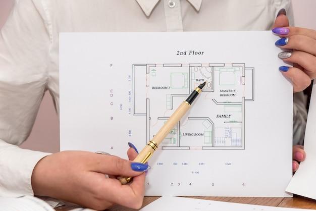 Mani femminili con la penna che indica al progetto della casa