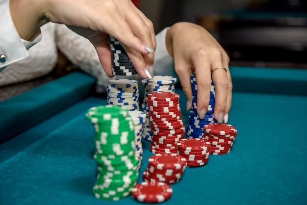 Mani femminili con pile di fiches da poker closeup