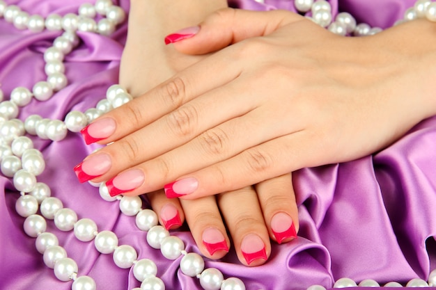 Mani femminili con manicure rosa su gioielli