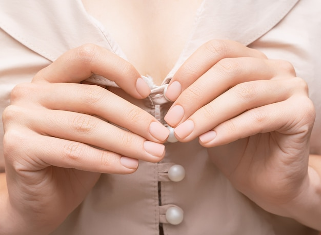 Mani femminili con unghie rosa. manicure con smalto rosa opaco. mani di donna su sfondo di tessuto rosa.