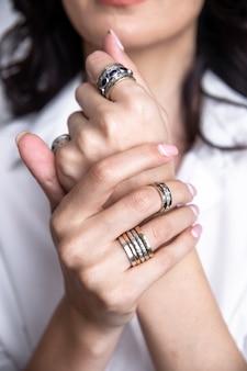 Mani femminili con anelli sulle dita.