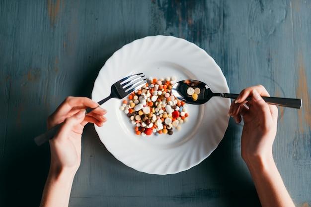 Mani femminili con cucchiaio e forchetta, piatto pieno di farmaci, vista dall'alto. concetto di dieta dimagrante