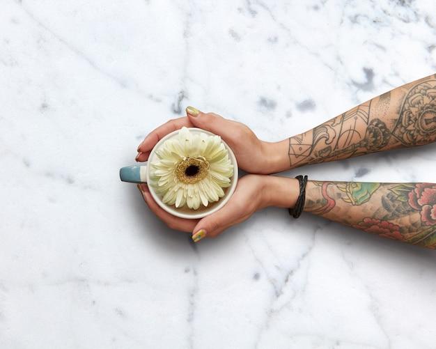 Mani femminili con tatuaggi che tengono una tazza di tè profumato con una gerbera bianca su una superficie di marmo naturale bianco. lay piatto. tempo di primavera. festa della mamma concetto