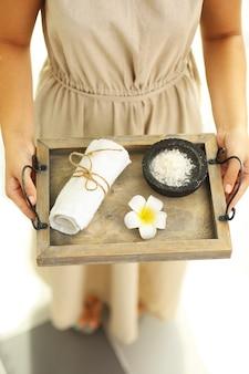Mani femminili con vassoio di prodotti termali, al salone della stazione termale