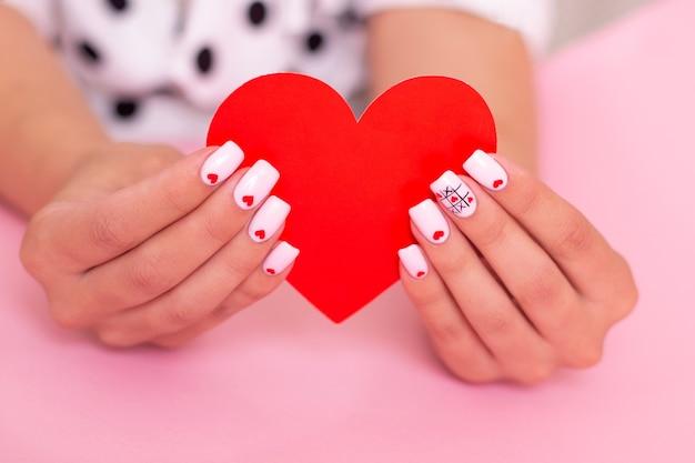 Mani femminili con design di cuori di unghie per manicure bianche