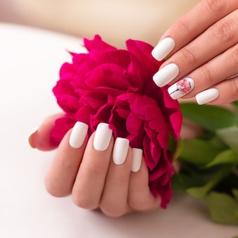 Mani femminili con unghie bianche per manicure design peonie