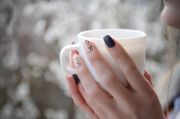 Mani femminili con una tazza bianca nelle mani