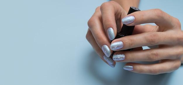 Mani femminili con manicure invernale e una bottiglia di smalto per unghie