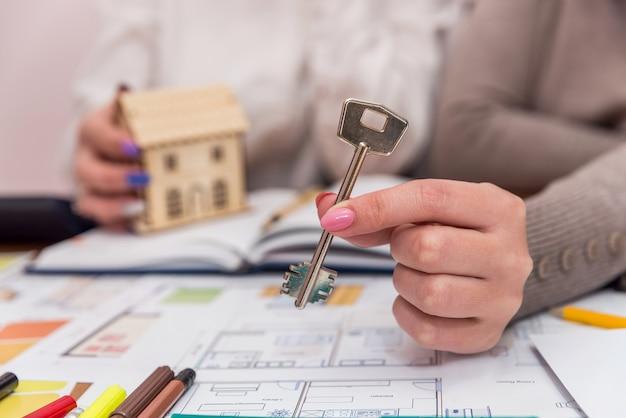 Mani femminili con modello di casa in legno e chiave