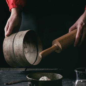 Mani femminili con mattarello e setaccio in legno