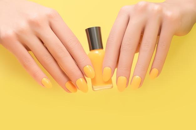 Le mani femminili con i disegni delle unghie gialle tengono una bottiglia di smalto giallo.