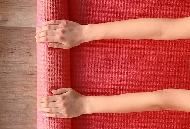 Mani femminili con materassino yoga, vista dall'alto