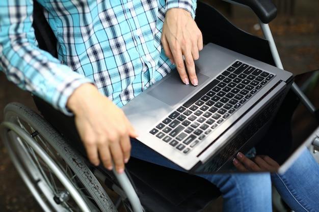 Mani femminili che lavorano al computer portatile mentre era seduto in sedia a rotelle