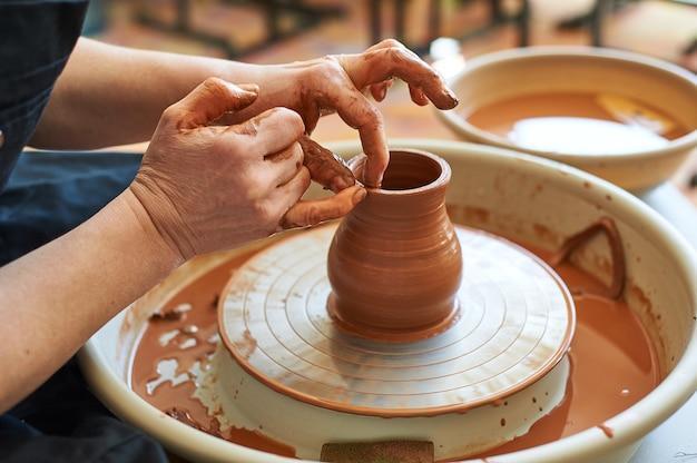Mani femminili che lavorano su un tornio da vasaio facendo una brocca.